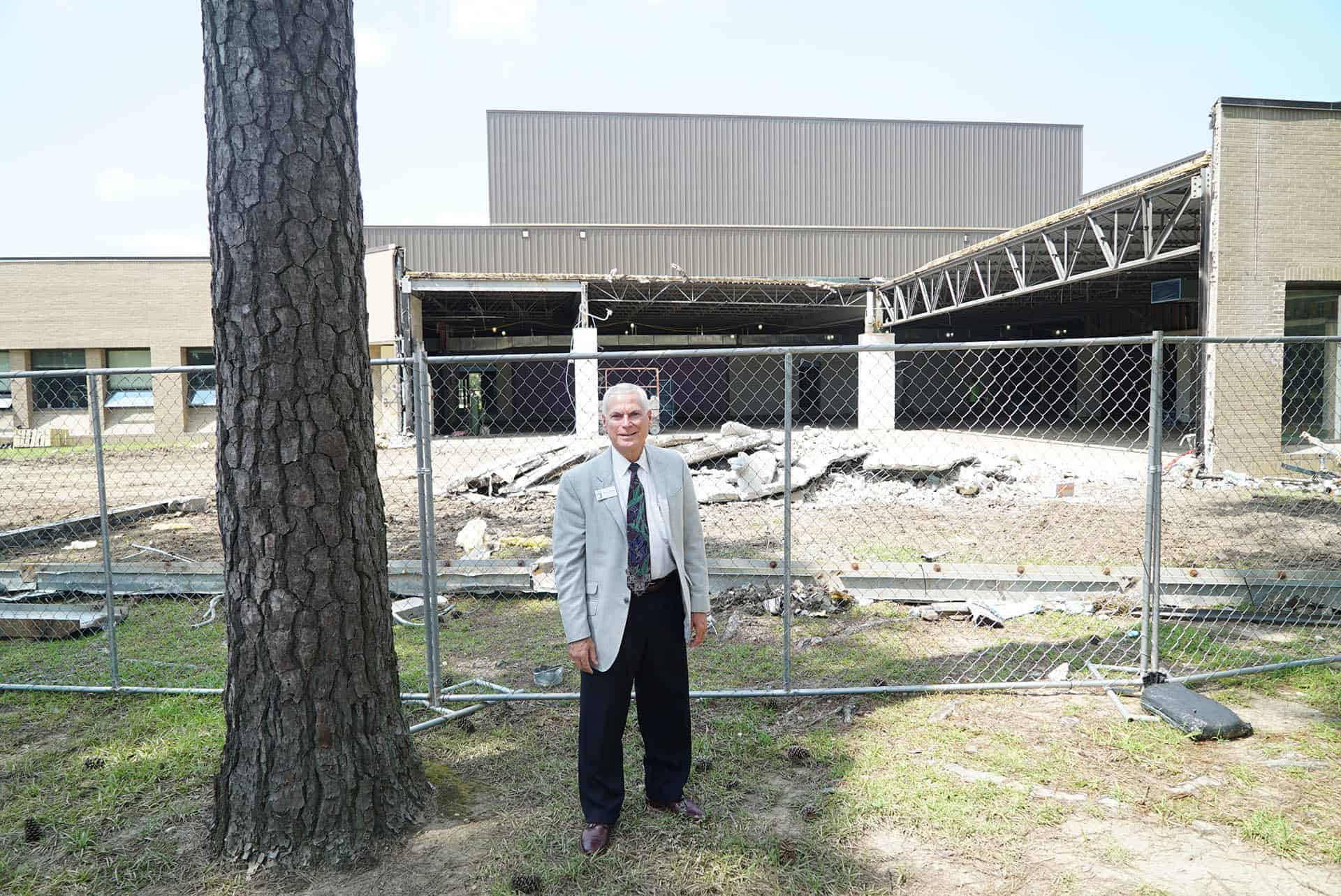 President Johnson stands in front of construction rubble